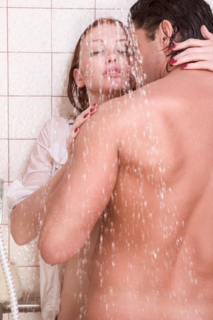 Loving affectionate young heterosexual couple in affectionate sensual kiss after taking shower. Mid adult Caucasian men in late 30s and young Caucasian redhead woman in early 20s photo