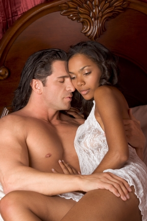Lovers � Interracial sensual couple making love in bed Stock Photo - 10690939