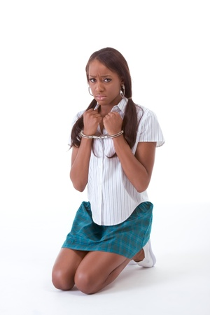 crime and abuse Ð handcuffed Ethnic black African-American sensual woman pretending to be schoolgirl student in uniform skirt