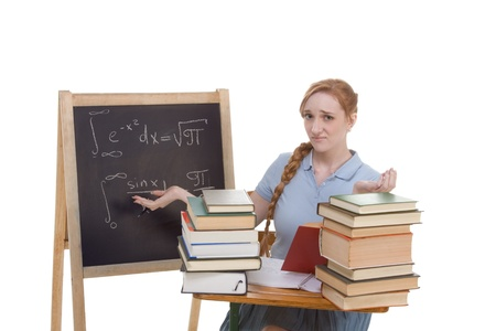High school or college Caucasian redhead woman student sitting by the desk. Blank blackboard with advanced mathematical formulas is visible in background photo