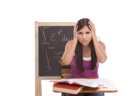 Stressed High school or college Latina female student sitting by the desk at math class. Blackboard with complicated advanced mathematical formals is visible in background