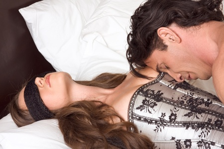 sex couple: heterosexual couple. Woman laying down on her back and eyes are covered by black scarf Stock Photo