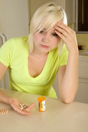 substance abuse: Caucasian woman by kitchen countertop with medicine bottle of medication drug pill
