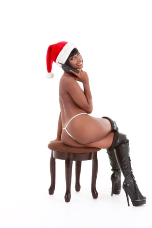 Sensual Naked erotic ethnic black woman in Mrs Santa Claus costume and Santa hat talking on sex phone Stock Photo - 11123619