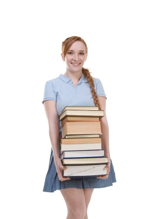 Young Caucasian female college student in jeans with backpack holding huge pile of educational books from library photo
