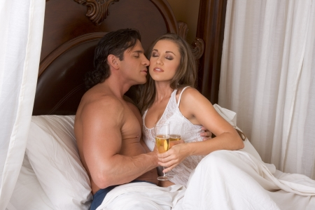 Young sexy heterosexual couple celebrating with wine in bed Stock Photo - 11209865