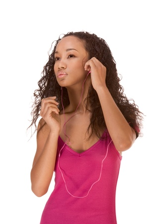 Young biracial dark skinned female of Chinese, African-American black and Middle Eastern origin in red tank top working out while listening to music from portable player fixed on her arm, with headphones attached to it photo