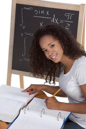 formals: High school or college African-American black female student sitting by the desk at math class. Blackboard with advanced mathematical formals is visible in background