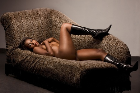 Portrait of young topless naked voluptuous sensual Hispanic woman in brown panties and black leather boots lying down on sofa wit her legs up photo