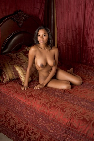 nude: Ethnic black nude multiethnic woman of Indian and African mix on red luxury bed Stock Photo