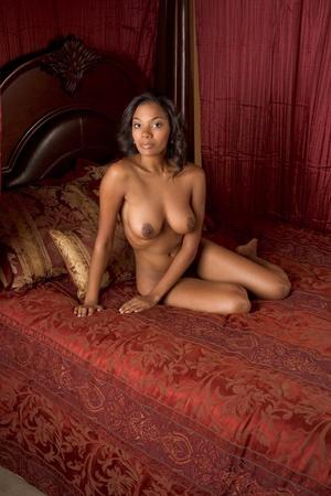 schwarze frau nackt: Ethnic schwarz nude multiethnischen Frau von indischen und afrikanischen Mix auf rotem Luxus Bett Lizenzfreie Bilder