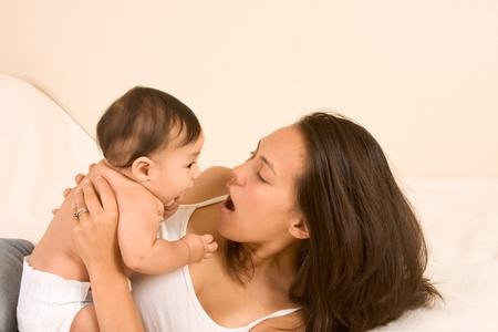 Mam� e hijo en la cama y la madre abrazando al beb� reci�n nacido jugando con �l photo