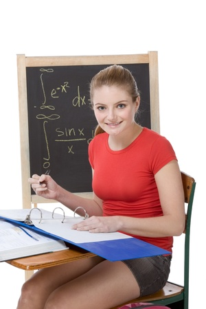 High school or college female student sitting by the desk at math class. Blackboard with advanced mathematical formals is visible in background photo