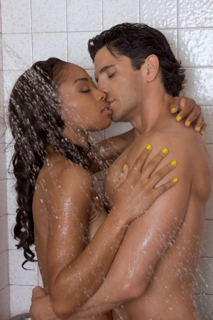 Loving affectionate nude heterosexual couple in shower engaging in sexual games, hugging and kissing. Mid adult Caucasian men in late 30s and young black African-American woman in 20s photo