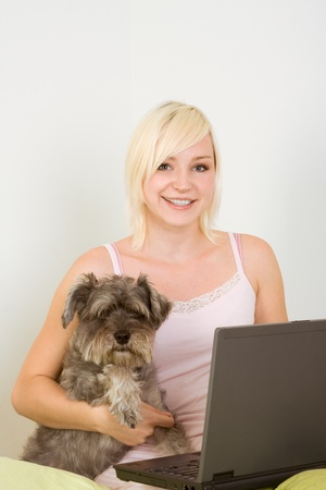 Caucasian blond young woman sitting on bed working on portable notebook pc computer together with dog of Schnauzer breed photo