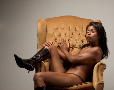 Portrait of young topless naked voluptuous sensual Hispanic woman in brown panties and black leather boots sitting on armchair, covering boobs by her shoulders photo