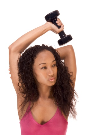 Young biracial dark skinned female of Chinese, African-American, German and Middle Eastern origin in red tank top fitness exercise work out with dumbbell