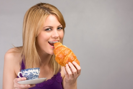 Friendly blonde female enjoying her cup of coffee with Croissant