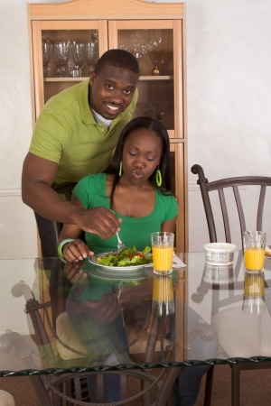 black dish: Young black African American couple sitting by glass table and eating meal of salad, bagels with cream cheese and orange juice