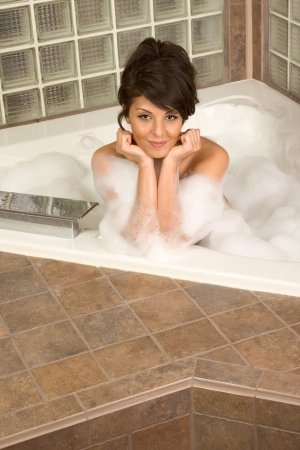 bathtub Sensual sexy female relaxing in hot tub bath with foam photo