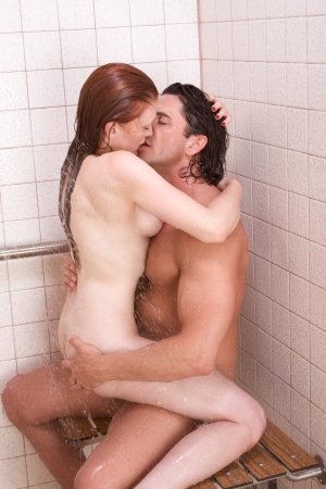 Loving affectionate nude young heterosexual couple in affectionate sensual kiss after taking shower. Mid adult Caucasian men in late 30s and young Caucasian redhead woman in early 20s