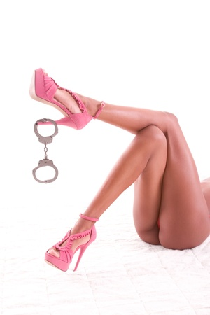 legs of naked sensual sexy black ethnic African-American woman in high-heel shoes with handcuffs dangling