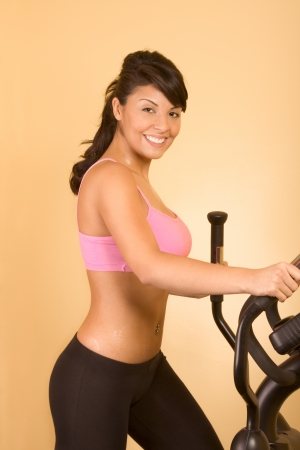 Young woman sweaty while working out on elliptical machine