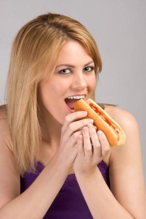 perro caliente: Hermosa rubia mujer morder pan de hot dogs con salchichas y salsa de tomate durante la pausa para el almuerzo. Foto de archivo