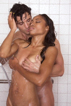 adult sex: Loving affectionate nude heterosexual couple in shower engaging in sexual games, hugging and kissing. Mid adult Caucasian men in late 30s and young black African-American woman in 20s