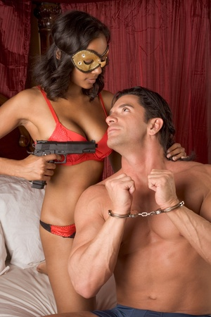 Lovers - Interracial sensual couple making love in bed. mystery love Woman in mask holding gun
