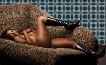 Portrait of young topless naked voluptuous sensual Hispanic woman in brown panties and black leather boots lying down on sofa wit her legs up Stock Photo