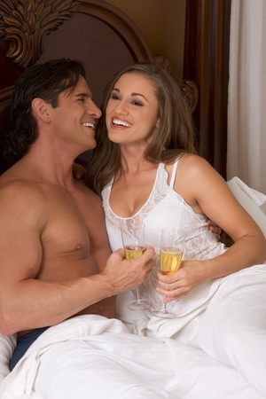 Young sexy heterosexual couple celebrating with wine in bed photo