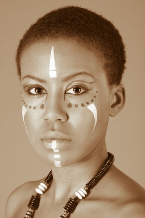 Portrait of African American woman wearing original tribal themed face-paint and necklace photo