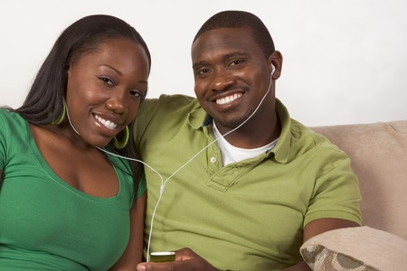 Young African American couple sitting in living room on couch enjoying time together and share usage of portable MP3 player, using the same headphones