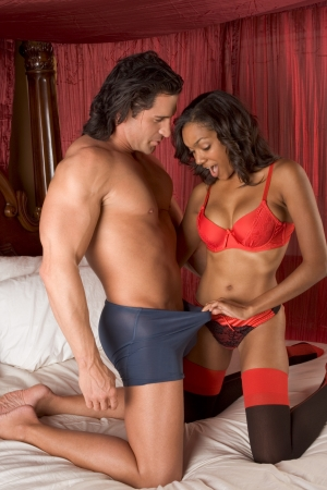 sex couple: Sensual woman in lingerie looking into panties of Caucasian man worried about his sexual performance and erectile dysfunction