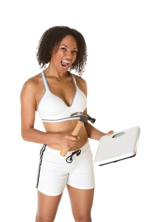 Ethnic woman in sporty outfit hits weight scales by hammer photo