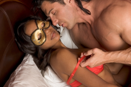 Lovers - Interracial sensual couple making love in bed. Mystery love Woman in mask Stock Photo - 12232239