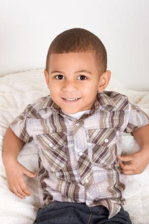 Jeune petit garçon sur le lit Banque d'images - 12232238