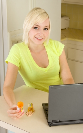 16 17: Caucasian woman by kitchen countertop with laptop PC computer and medicine bottle shopping for medication drugs online