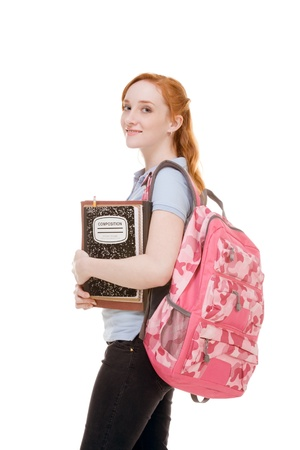 Friendly Caucasian High school girl student standing with backpack and holding books, notebooks and composition book
