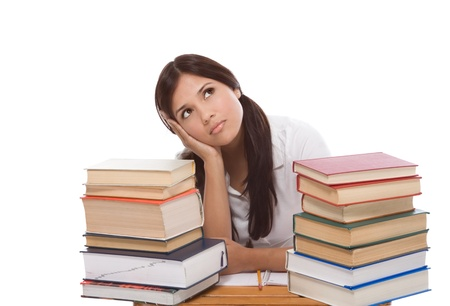 bored High school or college Latina female student sitting by the desk with pile of books in front of her Stock fotó