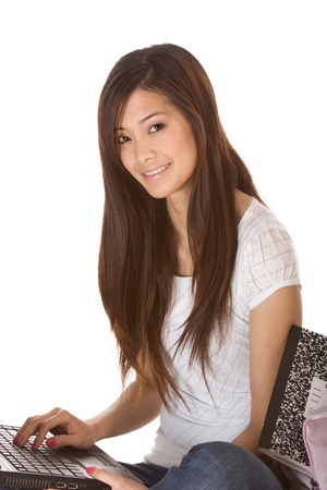 Friendly Asian High school girl student sitting in jeans with portable laptop PC computer photo