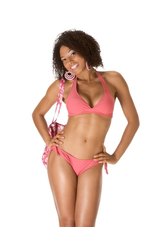 Dark skinned black female in pink swimsuit holding beach bag Stock Photo - 13211998