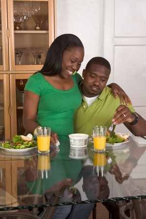 two people only: Young black African American couple sitting by glass table and eating meal of salad, bagels with cream cheese and orange juice