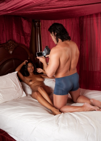 Sensual naked woman lying down on bed and man filming her on camcorder video camera Stock Photo - 13436264