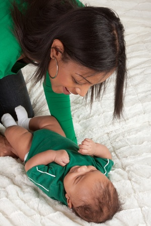 Biracial mom on bed with her multiethnic black infant son (baby is 3 months old) photo