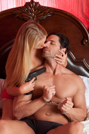Lovers - sensual couple making love in bed. Mystery woman in lingerie holding gun, man in handcuffs