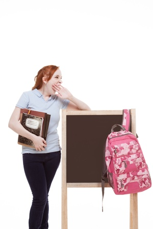 education series - Friendly Caucasian female high school student with backpack by blank blackboard with copy space