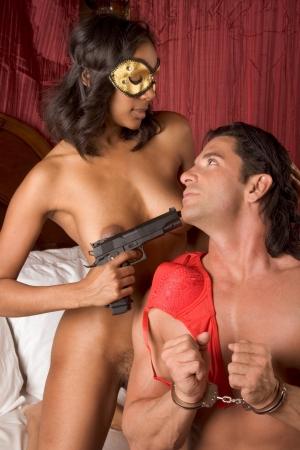 man and woman sex: Lovers - Межрасовый чувственный пара занимается любовью в постели. Тайна любви Женщина в маске пушки холдинг