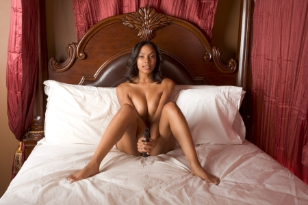topless brunette: mystery nude Ethnic black multiethnic woman of Indian and African in bed holding gun